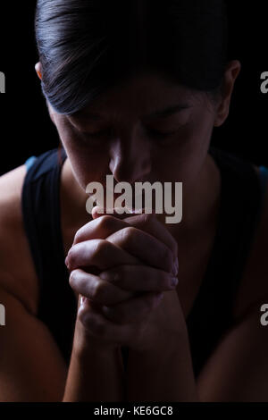 Low key portrait of a faithful woman praying, hands folded in worship to god, head down and eyes closed in religious - Stock Photo