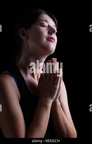 Happy faithful woman praying and smiling in happiness, bliss and peace, feeling inspired with the presence of god - Stock Photo