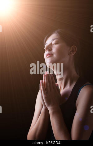 Faithful woman praying and smiling in happiness, bliss and peace, under a divine or celestial light feeling inspired - Stock Photo