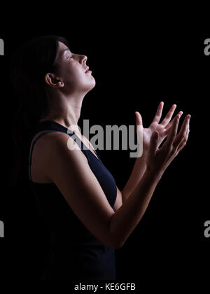 Low key of a faithful woman praying and feeling the presence or being touched by god. Arms outstretched in worship, - Stock Photo
