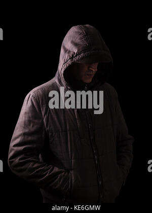Scary and creepy man hiding in the shadows, standing in the darkness / black background hood hiding face shadows - Stock Photo