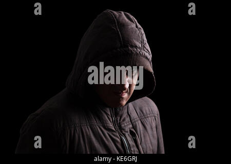 Man with repressed anger and violent instinct hiding in shadows. Standing in the darkness / angry passive aggressive - Stock Photo