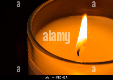 Close up of a burning scented jar candle - Stock Photo