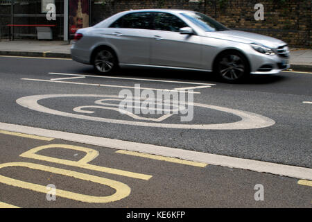 Silver Mercedes-Benz car travels along a road in a suburban 20 mph zone, London, England - Stock Photo