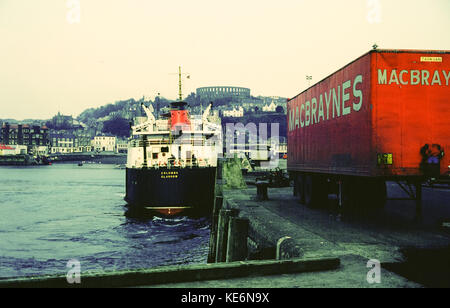 Columba, Caledonian MacBrayne ferry moored in Oban harbour, with McCaig's Tower and MacBrayne transport lorry, West - Stock Photo