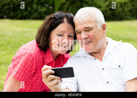 Happy Senior Couple Taking Selfie With Mobile Phone - Stock Photo
