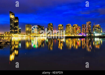 Still reflection of bright illuminated residential buildings towers Yarra river waterfront in Melbourne modern suburb - Stock Photo