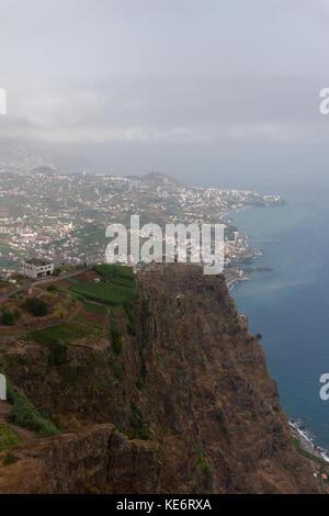 The steep cliifs of Cabo Girão and Câmara De Lobos rise steeply from the Funchal suburb of São Martinho - Stock Photo