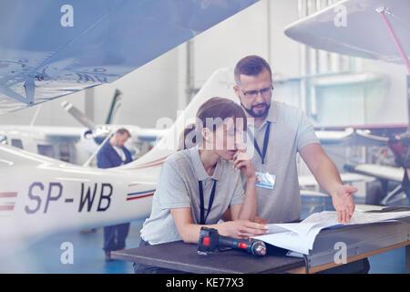 Airplane mechanics reviewing plans in hangar - Stock Photo
