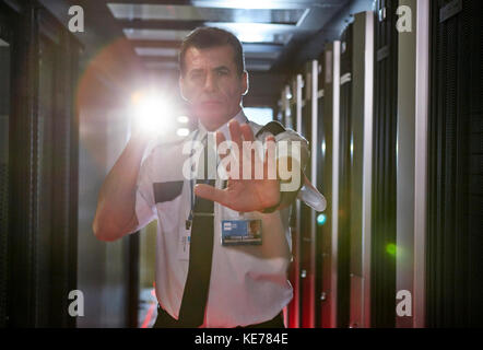 Portrait male security guard with flashlight gesturing stop in server room - Stock Photo