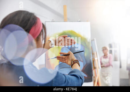 Female artist gesturing, framing painting on easel in art class studio - Stock Photo