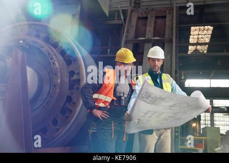 Engineers reviewing blueprints in steel factory - Stock Photo
