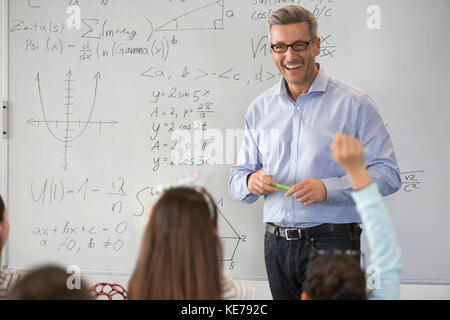 Smiling male science teacher leading lesson at whiteboard in classroom - Stock Photo