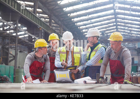 Male foreman, engineers and workers meeting in factory - Stock Photo