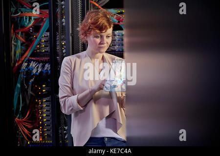 Female IT technician using futuristic digital tablet in server room - Stock Photo