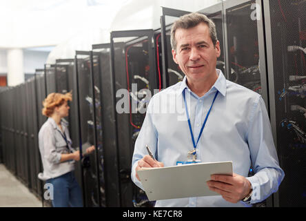 Portrait confident male IT technician with clipboard in server room - Stock Photo