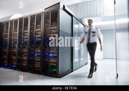 Male security guard walking in server room - Stock Photo