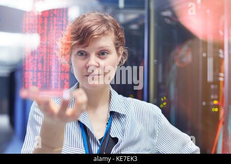 Female IT technician holding futuristic digital tablet in server room - Stock Photo