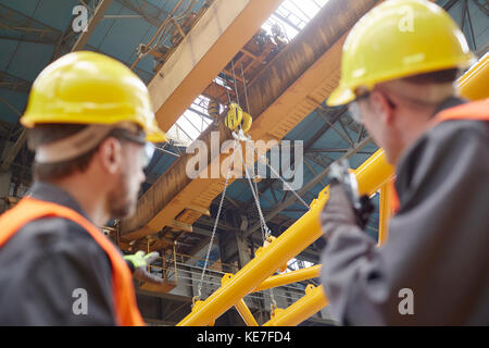 Male worker using walkie-talkie to guide hydraulic crane lowering equipment in factory - Stock Photo