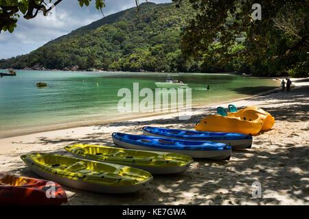The Seychelles, Mahe, Port Launay, plastic sea canoes on beach - Stock Photo