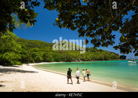The Seychelles, Mahe, Port Launay, beach and Pointe L'Escalier, visitors walking along shore - Stock Photo