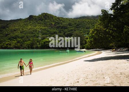The Seychelles, Mahe, Port Launay, beach couple walking along shore - Stock Photo