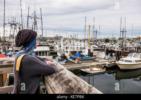 Young Woman Looks Out Over Fisherman's Wharf; Victoria, British Columbia, Canada - Stock Photo