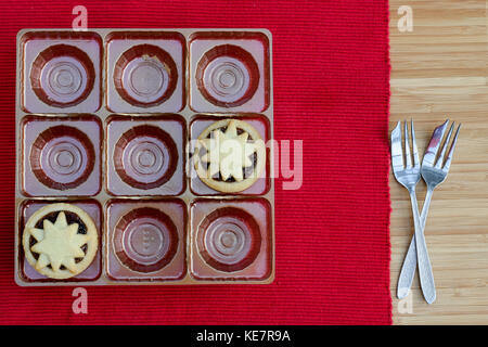 Two mince pies remaining in nine hole tray with two cake forks set on red mat - Stock Photo