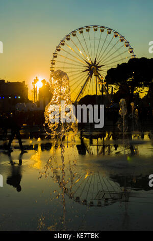 Fountain And A Ferris Wheel At Sunset Reflected In Water, Place Massena; Nice, Cote D'azur, France - Stock Photo