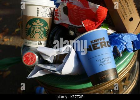 Non-recyclable coffee shop take away cups in street rubbish bin, London - Stock Photo