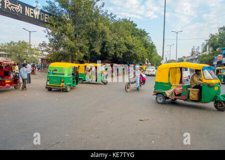 DELHI, INDIA - SEPTEMBER 25 2017: Unidentified people with a green rickshaws and an auto-rickshaws driving in the - Stock Photo