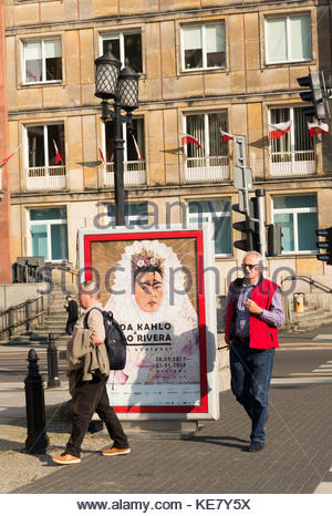 Advertisement board about the Frida Kahlo and Diego Rivera show on a street with two walking men on September 2017 - Stock Photo