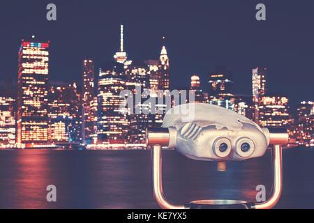 Vintage toned binoculars with New York City skyline at night, USA. - Stock Photo