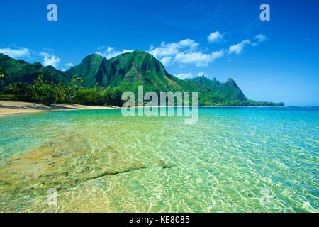 Clear turquoise ocean water and the rugged mountainous landscape on the island of Kauai; Kapaa, Kauai, Hawaii, United - Stock Photo
