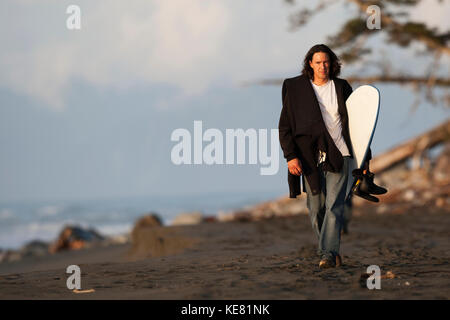 Surfer Walking With A Surfboard Along The Coast Near Yakutat, Southeast Alaska, USA - Stock Photo
