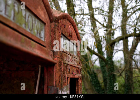 Close up of abandoned red telephone kiosks in reclamation yard. - Stock Photo