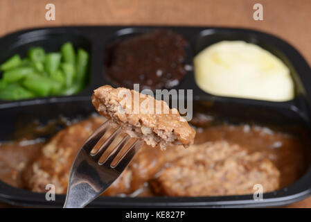 macro salisbury steak on a fork tv dinner - Stock Photo