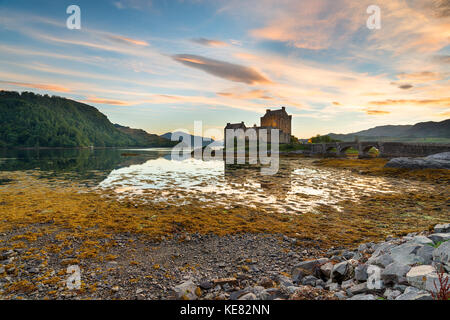 Sunset over Eilean Donan Donan Castle on the shores of Kyle of Lochalsh in the Highlands of Scotland - Stock Photo