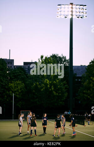 Sports Team Practice On A Field On The University Of Toronto Campus At Dusk; Toronto, Ontario, Canada - Stock Photo
