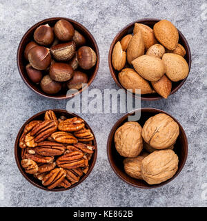Whole almonds,whole walnuts ,whole hazelnut and pecan nuts in wooden bowl setup with stone background.  Selective - Stock Photo