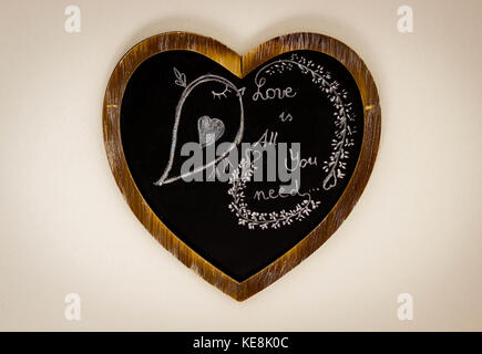 Heart Shape Drawing On Chalk Board with bird - Love is all you need - Stock Photo