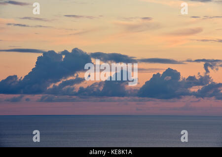 Dramatic sunset and horizon over calm Ionian Sea and cirrus, altostratus, cumulus, stratocumulus and stratus clouds - Stock Photo