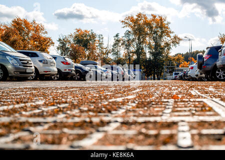 Tourists from different countries parked their cars in the parking lot. Modern cars are perfectly parked. Autumn - Stock Photo