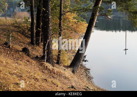 The shore of the forest lake in the autumn with a tarsar for jumping into the water - Stock Photo