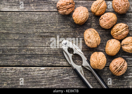 Tasty dried walnuts and nutcracker on old wooden table. Top view. - Stock Photo