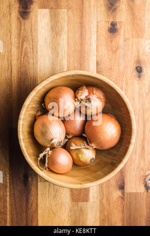 Fresh onion bulbs in wooden bowl. - Stock Photo