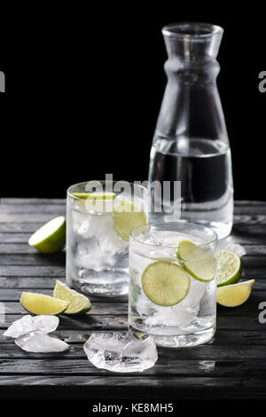 Selective focus composition with gin and tonic cocktail served with citrus on  wooden table with pieces of ice - Stock Photo