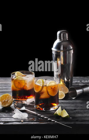 Selective focus composition with rum and cola cocktail served with  citrus on rough paper and fabrick over the wooden - Stock Photo