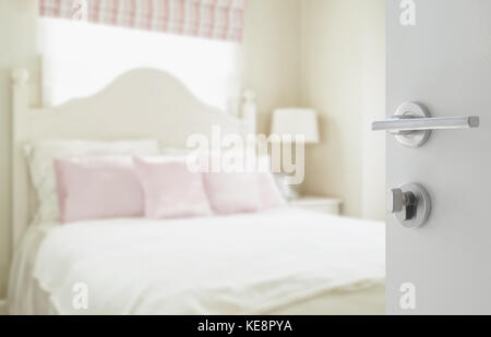 opened white door to luxury bedroom with pillows and desk lamp as blur background - Stock Photo