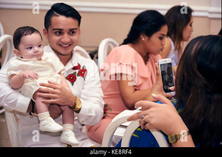 Godfather having his picture taken with the just christened baby at his baptismal party - Stock Photo
